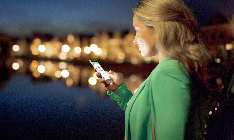 Overzicht thumb afbeelding veiligheid. Vrouw controleert in het donker haar telefoon